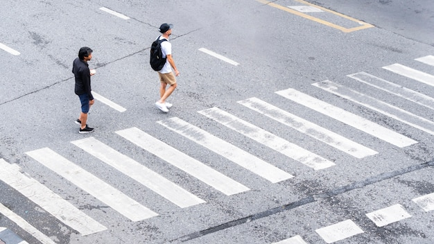 The busy city people move to pedestrian crosswalk on business traffic road.