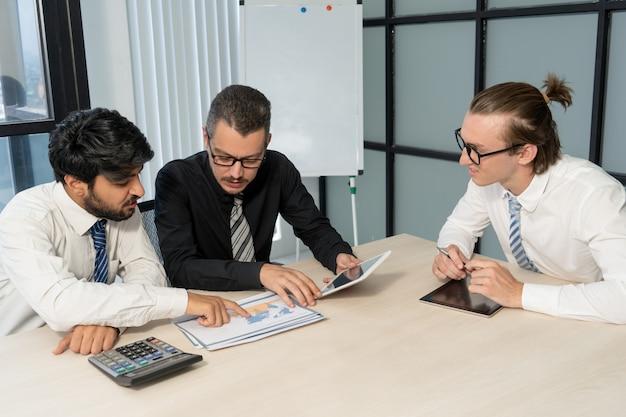 Занятые коллеги обсуждают международную экономику на встрече.