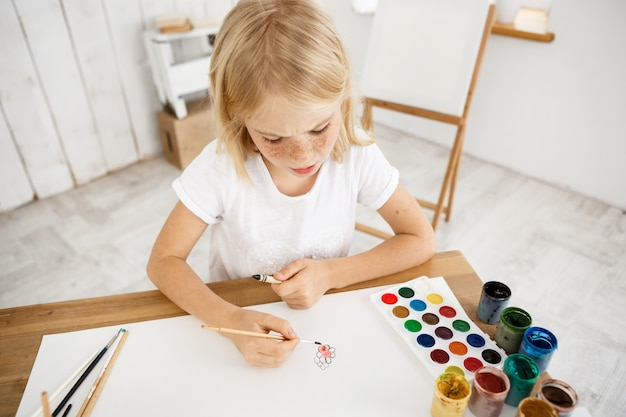 Busy and concentrated cute little blonde girl