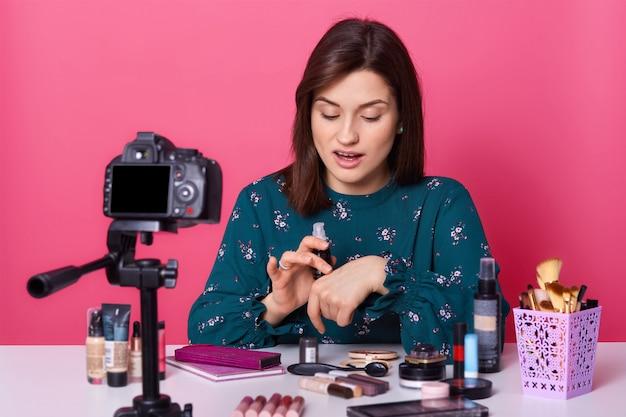 Занятый концентрированный визажист тестирует новое лицо перед камерой, одет в рубашку с цветочным принтом, выглядит впечатленным