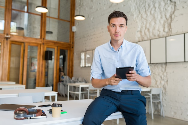 Busy confident young stylish smiling man in co-working office, startup freelancer holding using tablet,