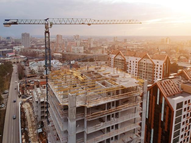 Оживленная строительная площадка и строительное оборудование аэрофотоснимок на закате.