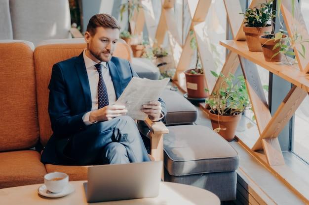 Занятый корпоративный сотрудник, одетый в синий костюм, сидит на удобном стуле в уютном кафе после заказа кофе, делает перерыв в работе, читает газету с открытым ноутбуком перед ним