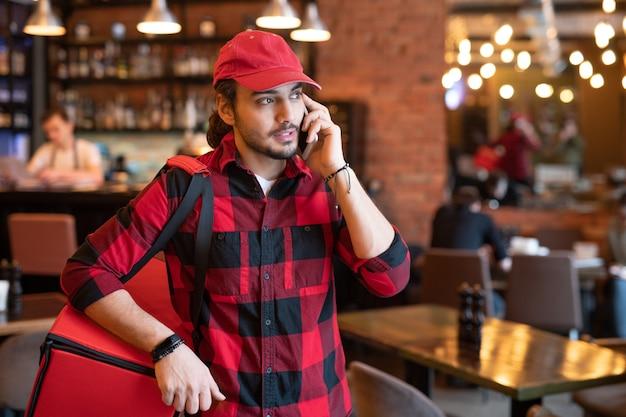 注文した食品の配達について住所と警告を求めている間、携帯電話でクライアントの1人と話している作業服の忙しい宅配便
