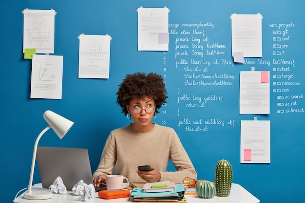 忙しい巻き毛のアフロ女性は自宅で仕事をし、職場でラップトップとスマートフォンを使用し、ニュースフィードをチェックし、フォルダーとメモ帳のある白い机でポーズをとります。