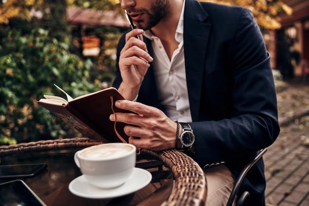 바쁜 하루. 야외 레스토랑에 앉아 있는 동안 개인 주최자의 메모를 확인하는 스마트 캐주얼 복장을 한 젊은 남자의 클로즈업