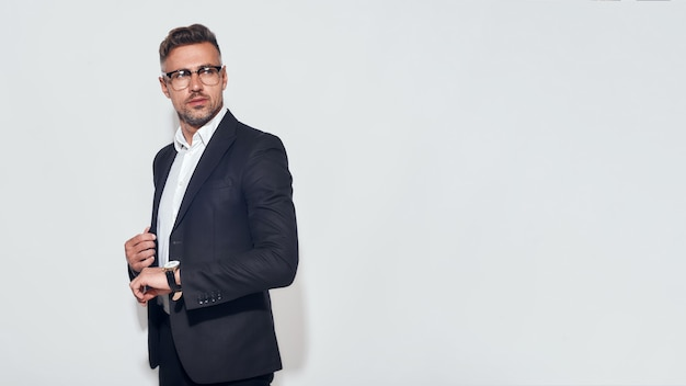 Busy day. handsome bearded businessman in classic suit and eyewear with watch on his hand standing against grey background. men beauty. business look. time concept