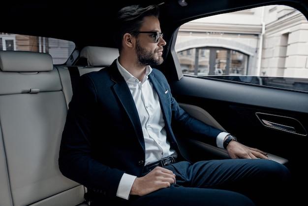 바쁜 하루. 차에 앉아있는 동안 창을 통해보고 전체 양복에 잘 생긴 젊은 남자