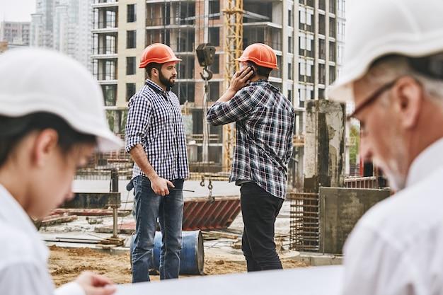 보호복을 입은 전문 엔지니어와 건축업자로 구성된 바쁜 하루 팀이 에서 함께 일하고 있습니다.
