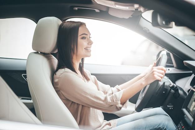 바쁜 하루. 차를 운전하는 동안 웃고 똑바로 바라보는 젊은 매력적인 여성