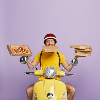 Busy deliveryman driving yellow scooter while holding pizza boxes