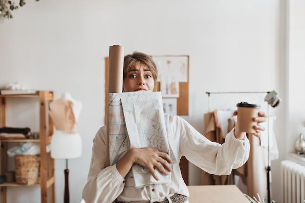 忙しいデザイナーの女性はコーヒーカップを保持します