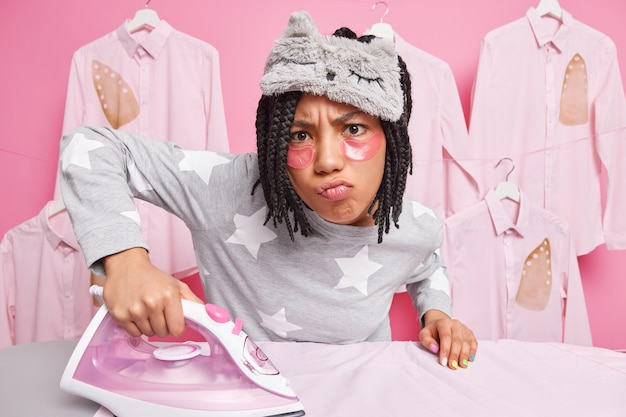 Busy displeased housewife does ironing makes unhappy grimace at camera dressed in nightwear irons husbands clothes poses against pink wall Free Photo