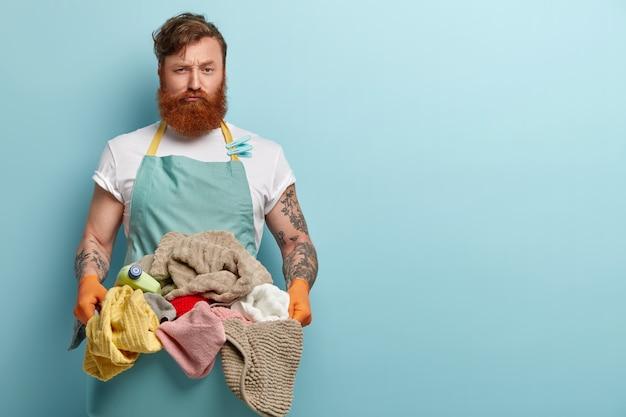 바쁜 불만족스러운 빨간 머리 남자가 세탁물로 가득 찬 대야를 세탁기로 옮기고 열심히 일하고 가사 일로 화가났습니다.