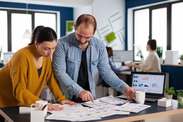 시작 사무실의 노트북 앞에서 연간 통계를 분석하는 바쁜 다양한 직원. 컴퓨터에서 회사 재무 보고서를 분석하는 다양한 기업인 팀.