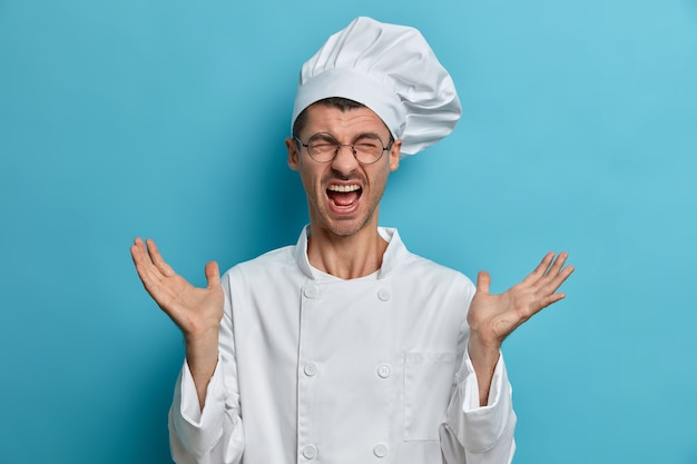 Un cuoco emotivo impegnato alza le mani e urla forte, ha molto lavoro in cucina, indossa occhiali rotondi, divisa bianca, litiga con il cuoco