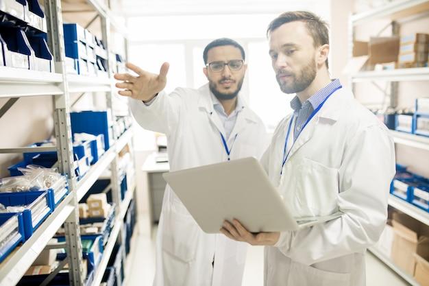 デバイスの記録を保管する忙しい工場のラボ技術者