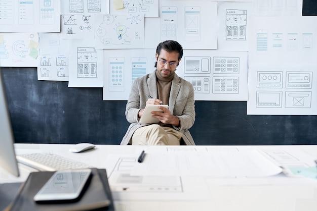 インターフェーススケッチでボードに座って、新しいデザインプロジェクトに取り組んでいるメガネで忙しいファッショナブルな男