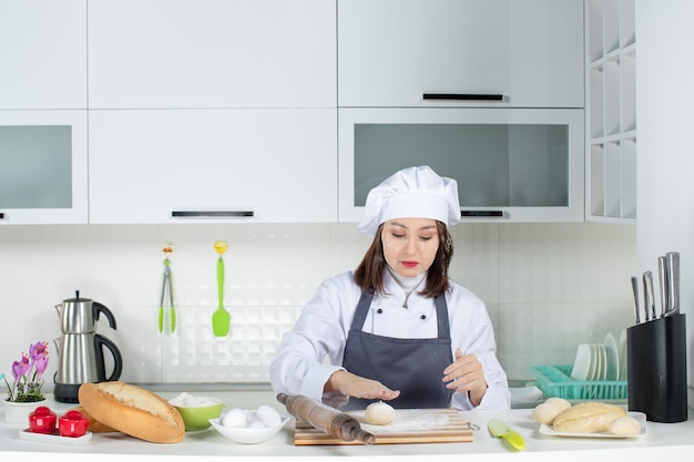 Impegnata chef commis in uniforme in piedi dietro il tavolo che si macchia il viso con la farina nella cucina bianca
