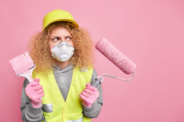 Busy female decorator holds brush and roller going to do house renovation looks attentively at wall she should paint poses in safety clothing against pink wall