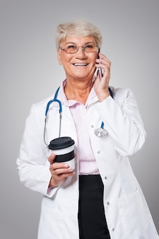 Busy female doctor with smartphone
