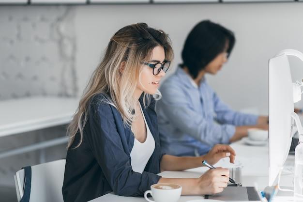 タブレットで作業し、コーヒーを飲む長い髪の忙しい女性フリーランサー。教室でコンピューターを使用して集中日本人学生の屋内の肖像画。