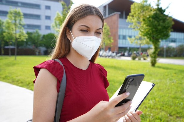 Ffp2kn95保護マスクを持った忙しい女性マネージャーが会社のオフィスの外を歩いているときにスマートフォンをチェックしています