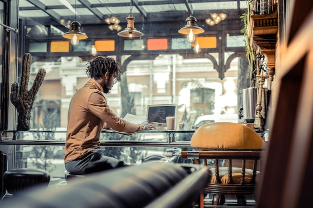 忙しいフリーランサー。彼のプロジェクトで働いている間半位置に座っている深刻な男性