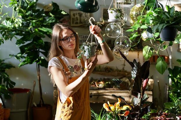 바쁜 정원사는 화분과 녹색 열대 관엽 식물 위에 화분에 심은 집 식물이있는 상점에서 일합니다.