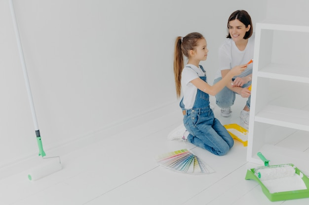 Busy girl and her smiling mother paint drawer in white color