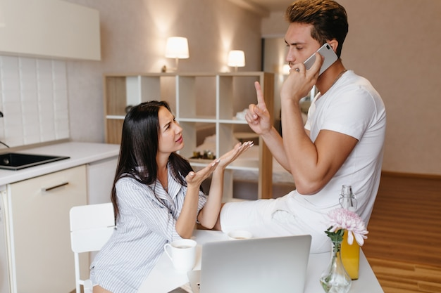 Busy guy talking on phone during lunch with wife in home