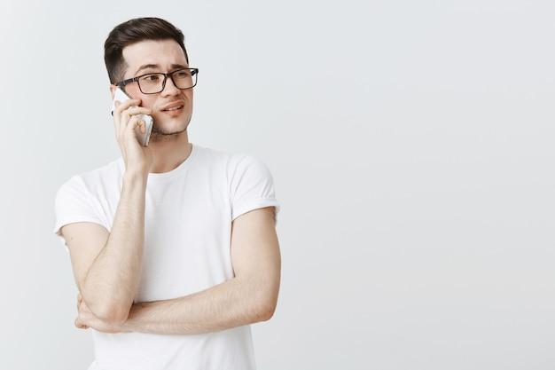 Ragazzo impegnato parla al telefono e sembra perplesso