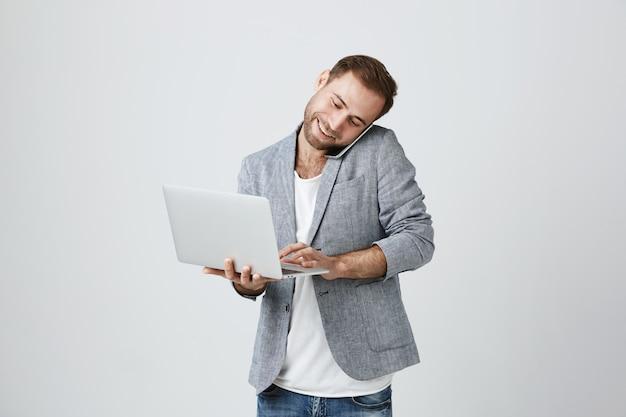 Занят красивый бизнесмен говорит по телефону и с помощью ноутбука