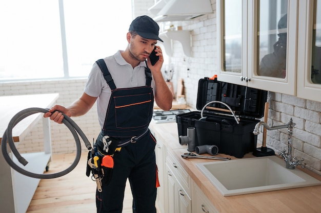 Busy handyman talk on phone in the kitchen