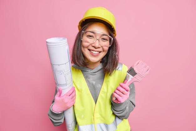 바쁘게 일하는 아시아 여성 건축업자는 건축 계획을 준비하고 집 재장식을 위해 페인트 붓을 들고 안전복 포즈를 취합니다