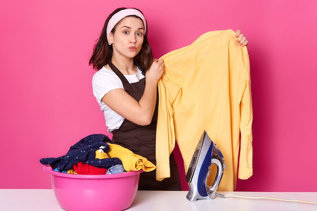 Занятая трудолюбивая черноволосая домохозяйка делает глажку после стирки