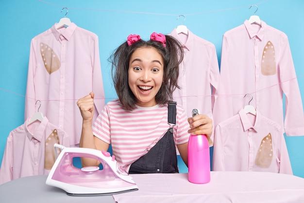 忙しい勤勉な女の子は拳を握りしめ、焦げたアイロンをかけたシャツに対して家事を終えることを祝います。