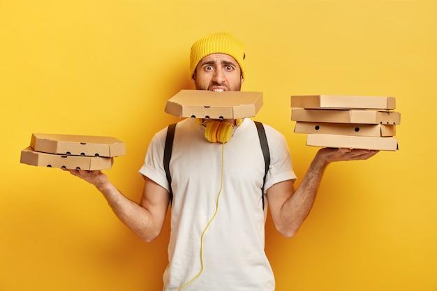 Un pizzaiolo impegnato e lavora sodo porta molte scatole di cartone con entrambe le mani e la bocca, ha molto lavoro, è un corriere professionale, indossa un cappello giallo e una maglietta bianca, offre uno spuntino delizioso per il cliente
