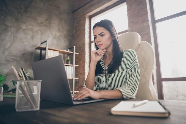 Занятая трудолюбивая бизнес-леди сидит за столом в офисе и думает на ноутбуке