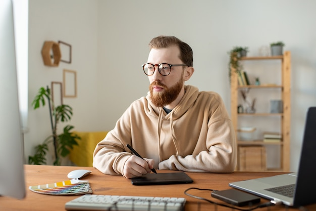 나무 책상에 앉아 그림을 만드는 동안 태블릿을 사용하여 수염을 가진 바쁜 힙 스터 만화가