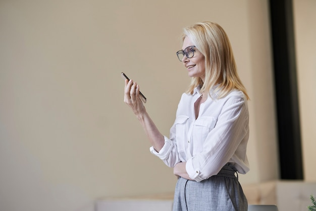 Busy hours stylish mature blonde woman in glasses and business attire smiling and talking on the