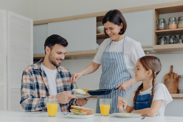 Busy housewife holds frying pan, gives prepared meal to husband and daughter, have delicious breakfast together