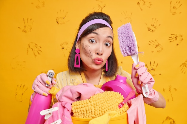 Busy housewife tries to keeps everything tidy has lips folded responsible for doing daily chores holds brush for dusting and cleaning detergent poses near laundry basket isolated on yellow wall