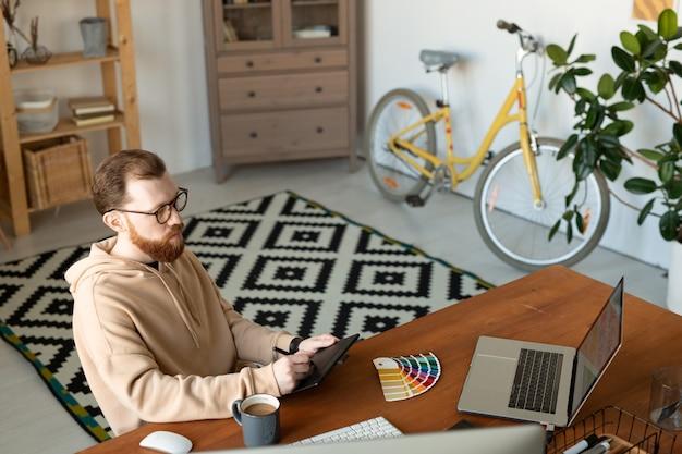 ホームオフィスに座って、描画タブレットを使用してスケッチを作成するパーカーで忙しいイラストレーター