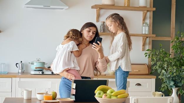 忙しいイライラした母親がリモートで仕事をしようとする娘が母親の仕事を邪魔する