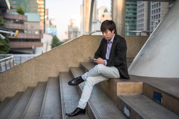 바쁜 한국 40대 사업가는 계단에 앉아 현대 도시에서 프로젝트 계획과 회의 일정을 확인합니다. 해질녘 도시 마을에서 운송하는 동안 휴대전화 작업을 합니다.