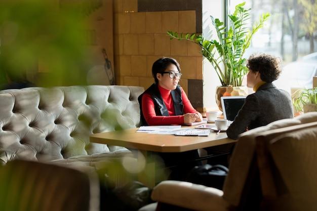 Занятые дамы разговаривают в современном кафе