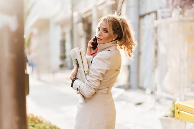 電話で話しながら肩越しに見ているトレンディなヘアスタイルで忙しい女性
