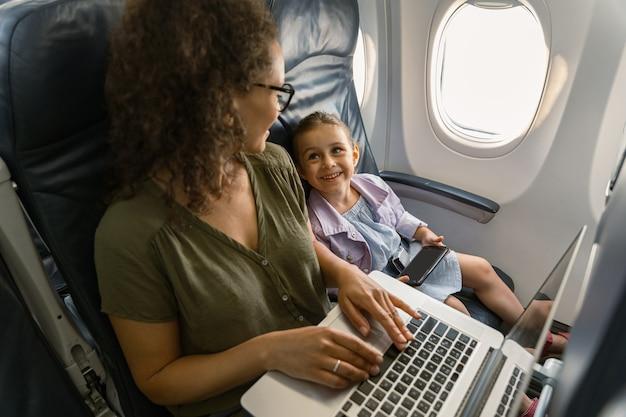 ラップトップで作業し、飛行機で旅行中に彼女の子供を見ている忙しい女性