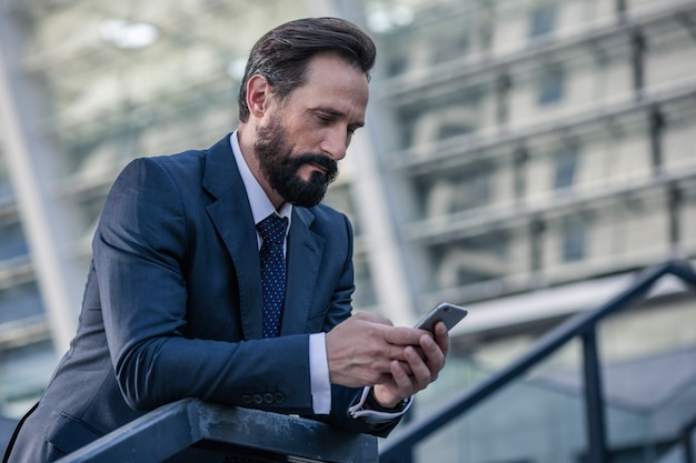Busy life. waist up of a bearded concentrated businessman holding a phone while leaning on the handrail